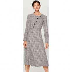 Sukienka z kontrastowymi guzikami - Wielobarwn. Szare sukienki z falbanami marki Mohito, z kontrastowym kołnierzykiem. Za 179,99 zł.
