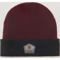 Dwukolorowa czapka z aplikacją - Bordowy. Czerwone czapki zimowe męskie marki House, z aplikacjami. Za 29,99 zł.