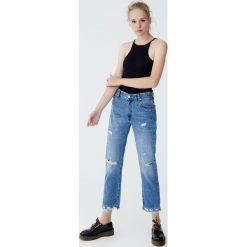 Rozszerzane jeansy z przetarciami. Niebieskie jeansy damskie Pull&Bear. Za 99,90 zł.