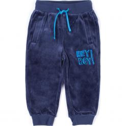 Spodnie. Niebieskie chinosy chłopięce HEY BOY, z nadrukiem, z bawełny. Za 29,90 zł.