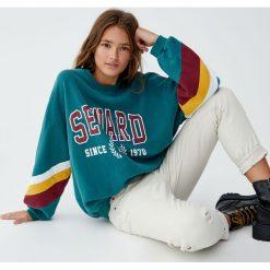 Bluza z napisem i panelami na rękawach. Fioletowe bluzy damskie marki NA-KD, z napisami, z długim rękawem, długie, z kapturem. Za 89,90 zł.