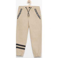 Spodnie jogger - Beżowy. Brązowe spodnie chłopięce marki Reserved. W wyprzedaży za 29,99 zł.