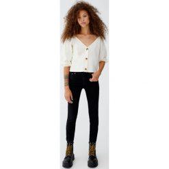 Jeansy skinny fit ze średnim stanem. Czarne jeansy damskie relaxed fit marki Pull&Bear, z jeansu. Za 69,90 zł.