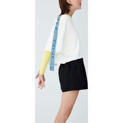 Sportowa koszulka z taśmami. Białe bluzki sportowe damskie Pull&Bear, z krótkim rękawem. Za 69,90 zł.