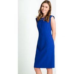 Kobaltowa sukienka z ozdobnym dekoltem QUIOSQUE. Niebieskie sukienki na komunię marki QUIOSQUE, w kolorowe wzory, wizytowe, z kwadratowym dekoltem. W wyprzedaży za 99,99 zł.