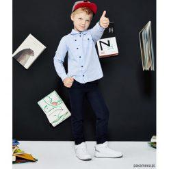 Koszula dziecięca dla chłopca Oxford Shirt Blue. Niebieskie koszule chłopięce z długim rękawem Pakamera, z asymetrycznym kołnierzem. Za 109,00 zł.