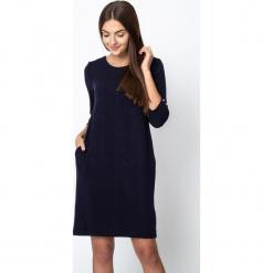 Granatowa błyszcząca sukienka wiązana na plecach QUIOSQUE. Szare sukienki balowe marki QUIOSQUE, do pracy, z dzianiny, z dekoltem na plecach, z długim rękawem, proste. W wyprzedaży za 159,99 zł.