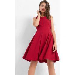 Rozkloszowana sukienka. Czerwone sukienki asymetryczne Orsay, do pracy, z elastanu, biznesowe, z asymetrycznym kołnierzem. Za 149,99 zł.