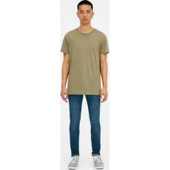 Ciemne jeansy skinny fit z efektem sprania i zużycia. Niebieskie rurki męskie marki Pull&Bear, z denimu. Za 119,00 zł.