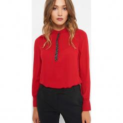 Koszula z koralikami. Czerwone koszule wiązane damskie Orsay, z poliesteru, eleganckie, ze stójką, z długim rękawem. Za 89,99 zł.