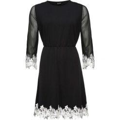 Sukienka z dżerseju z siatkową wstawką i koronką bonprix czarny. Czarne sukienki koronkowe marki bonprix, w koronkowe wzory, z kontrastowym kołnierzykiem. Za 89,99 zł.