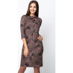 Wzorzysta sukienka z wiązaniem z przodu QUIOSQUE. Czerwone długie sukienki marki QUIOSQUE, na imprezę, na jesień, z nadrukiem, z dzianiny, z dekoltem na plecach, z długim rękawem. W wyprzedaży za 139,99 zł.