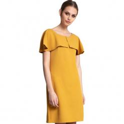 Sukienka w kolorze żółtym. Żółte sukienki na komunię marki Almatrichi, s, z dekoltem na plecach, midi, proste. W wyprzedaży za 199,95 zł.
