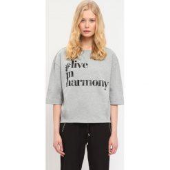 BLUZA NIEROZPINANA DAMSKA Z NADRUKIEM. Czerwone bluzy z nadrukiem damskie marki KALENJI, z elastanu, z krótkim rękawem, krótkie. Za 39,99 zł.