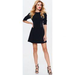 SUKIENKA CZARNA ROZKLOSZOWANA Z OZDOBNYMI WIĄZANIAMI W TALII. Czarne sukienki balowe Top Secret, na jesień, rozkloszowane. Za 79,99 zł.