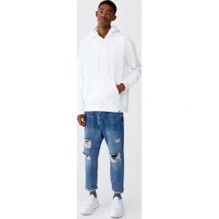 Jeansy relaxed fit z przetarciami. Niebieskie jeansy męskie relaxed fit Pull&Bear. Za 159,00 zł.