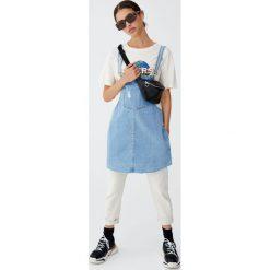 Jeansowa sukienka ogrodniczka z niewykończonym dołem. Szare sukienki z falbanami Pull&Bear, z jeansu. Za 89,90 zł.