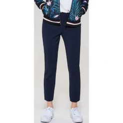 Spodnie typu chino - Granatowy. Czarne chinosy męskie marki KIPSTA, z poliesteru, do piłki nożnej. Za 89,99 zł.