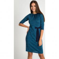 Niebieska błyszcząca sukienka z kokardą QUIOSQUE. Niebieskie sukienki balowe marki QUIOSQUE, na imprezę, z materiału, z dekoltem w łódkę, z długim rękawem, mini. Za 199,99 zł.