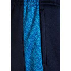 Under Armour Spodnie treningowe midnight navy. Niebieskie spodnie chłopięce marki Under Armour, z materiału. W wyprzedaży za 132,30 zł.