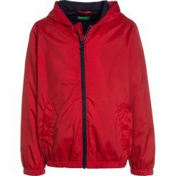 Benetton Kurtka przeciwdeszczowa red. Czerwone kurtki chłopięce przeciwdeszczowe marki Benetton, z materiału. Za 129,00 zł.