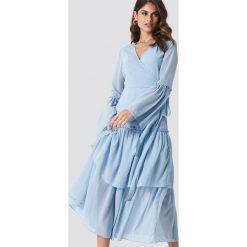 Andrea Hedenstedt x NA-KD Kopertowa sukienka maxi z falbaną - Blue. Niebieskie długie sukienki Andrea Hedenstedt x NA-KD, z poliesteru, z kopertowym dekoltem, z długim rękawem, kopertowe. W wyprzedaży za 170,07 zł.