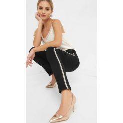 Spodnie z lampasami. Czarne rurki damskie marki Orsay, xs, z bawełny, z dekoltem na plecach. Za 119,99 zł.