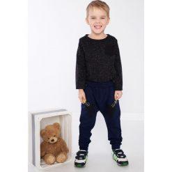 Czarna bluzka chłopięca z kieszonką DZ9027. Czarne spodnie chłopięce marki Fasardi, m, z dresówki. Za 39,00 zł.