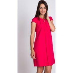 Malinowa sukienka z ozdobą na dekolcie QUIOSQUE. Różowe sukienki balowe marki QUIOSQUE, na co dzień, z tkaniny, z okrągłym kołnierzem, z krótkim rękawem, mini, plisowane. W wyprzedaży za 119,99 zł.