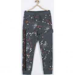 Spodnie. Brązowe chinosy chłopięce FUTURE, z nadrukiem, z bawełny. Za 79,90 zł.