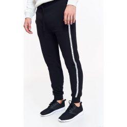 SPODNIE DŁUGIE MĘSKIE LUŹNE. Szare spodnie dresowe męskie marki Top Secret, w ażurowe wzory. Za 49,99 zł.
